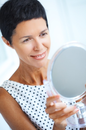 lifestyle looking lovely: Portrait of beautiful middle aged woman looking at cosmetic mirror Stock Photo