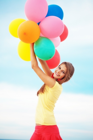 dynamic activity: Happy girl holding bunch of colorful air balloons at the beach