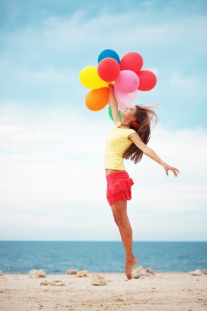 Happy girl holding bunch of colorful air balloons at the beach