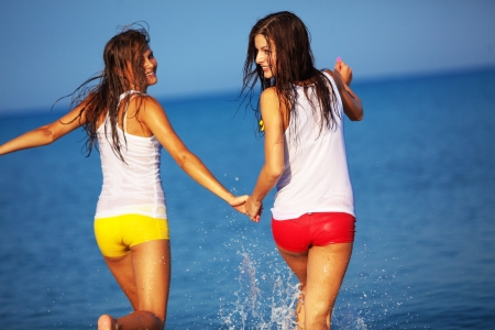 Beautiful girls having fun in water at beach photo