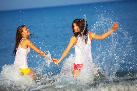 Beautiful girls having fun in water at beach photo