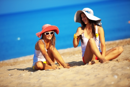 tanned girl: Beautiful young girls resting at the beach in hot summer Stock Photo