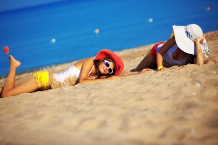 weekend activities: Beautiful young girls resting at the beach in hot summer Stock Photo