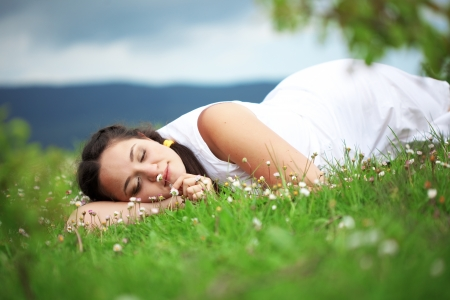 Casual outdoor portrait of young beautiful woman resting at spring nature photo