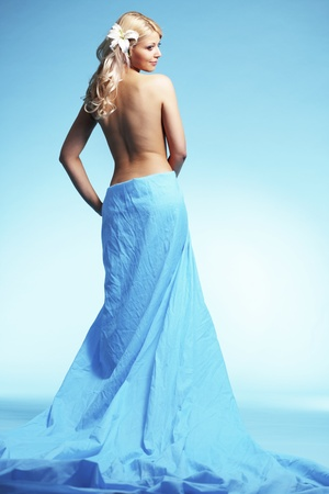 Portrait of very beautiful woman wearing long dress over blue photo