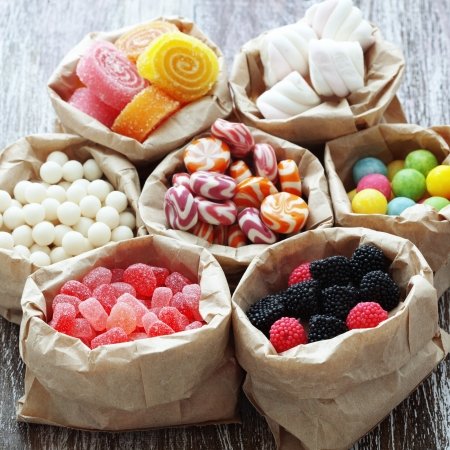 Muchos caramelos surtidos dulces de azúcar en el fondo de madera de época Foto de archivo