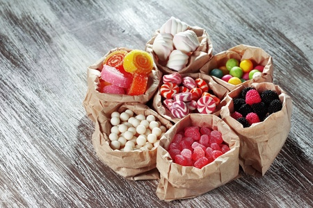 Many assorted sweet sugar candies on vintage wooden background photo