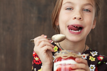 lick: Portrait of a child eating sweet homemade dessert with berries