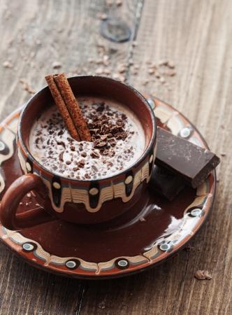 chocolate caliente: Copa de cacao del chocolate caliente con canela pega sobre fondo de madera de época enfoque, selectivo Foto de archivo