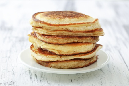 Stack of pancakes on vintage white wooden background photo