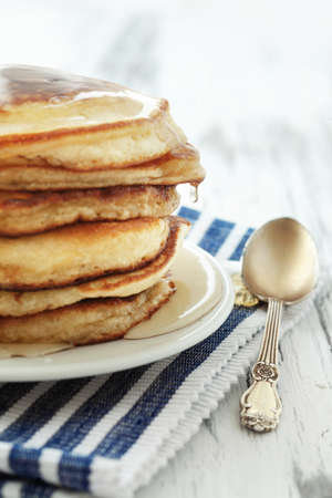 Stack of pancakes with honey on vintage white wooden background photo