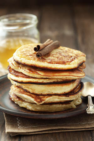 Stack of pancakes with honey on wooden background photo