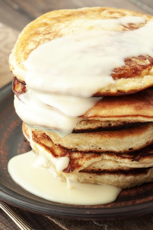 Stack of pancakes with condensed milk on wooden background photo