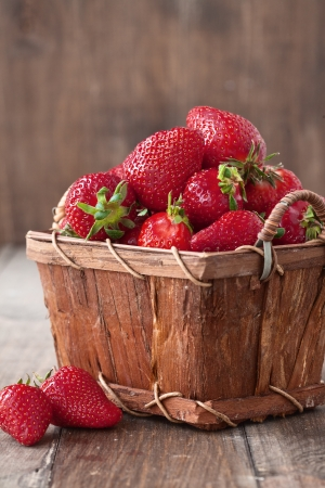 Fresh ripe strawberries in vintage basket on a wooden background photo