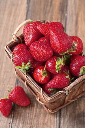 organic background: Fresh ripe strawberries in vintage basket on a wooden background Stock Photo