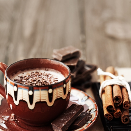 Cup of hot chocolate cocoa with cinnamon sticks on vintage wooden background, selective focus photo