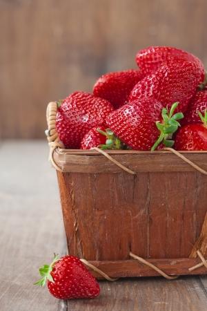 fresh strawberries: Fresh ripe strawberries in vintage basket on a wooden background Stock Photo