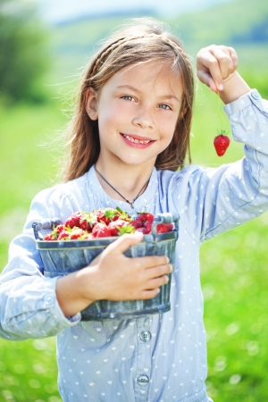 strawberry baskets: Child eating strawberries in a spring floral field