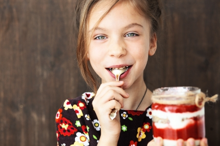 jam jar: Portrait of a child eating sweet homemade dessert with berries