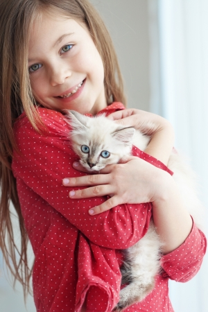 Home portrait of adorable child with small kitten Stock Photo