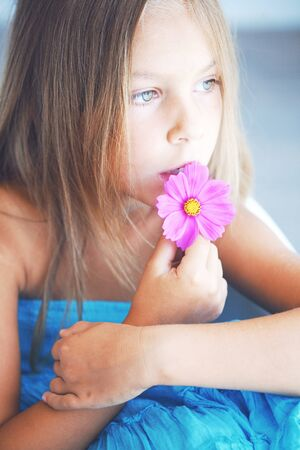 Kid girl with a flower closeup portrait photo