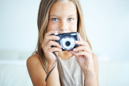 Little girl with compact photo camera
