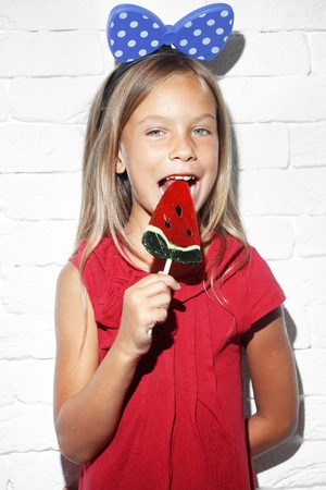 Child holding big lollipop over white brick wall photo