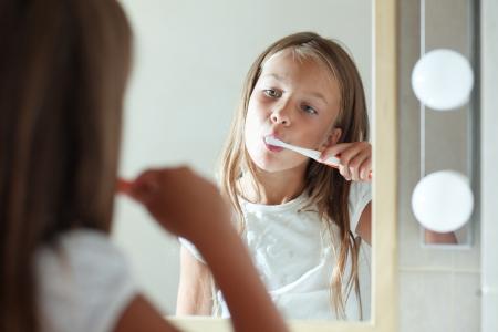 girl teeth: Little girl brushes teeth in the bathroom