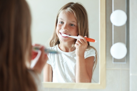 Little girl brushes teeth in the bathroom photo