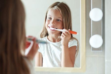 Little girl brushes teeth in the bathroom