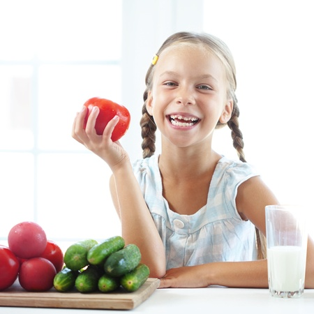 7 years old: Child eating vegetables in the kitchen at home
