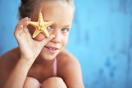 Child holding seashell on blue background photo