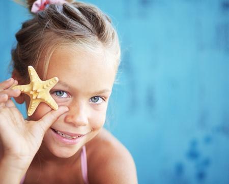 preteens beach: Child holding seashell on blue background