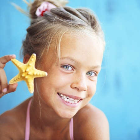 Child holding seashell on blue background