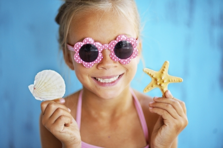 preteens beach: Child holding seashell on blue background