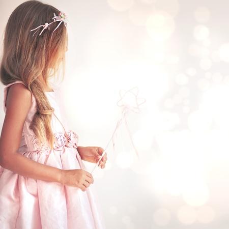魔法の杖と妖精の衣装を着て美しい少女