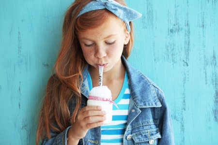 redheaded: Cute redheaded child drinking milk on vintage blue background