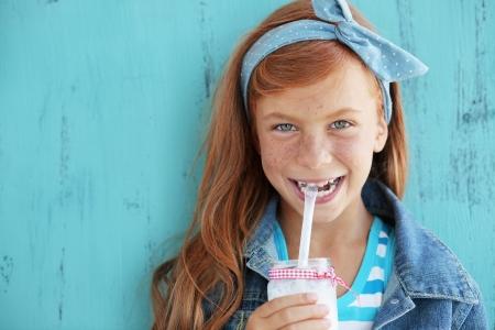 mleko: Śliczna ruda dziecko pije mleko na vintage niebieskim tle Zdjęcie Seryjne