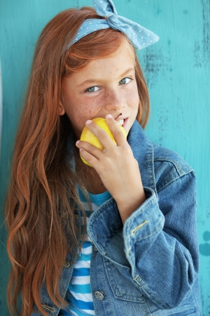 Cute redheaded child eating apple on vintage blue background photo