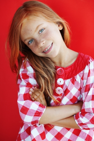 Cute redheaded child on red background photo