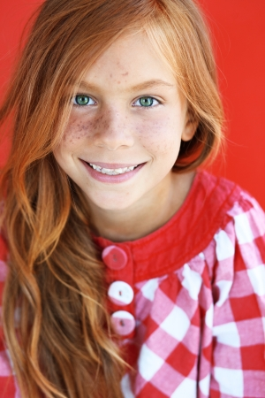 Cute redheaded child on red background Stock Photo
