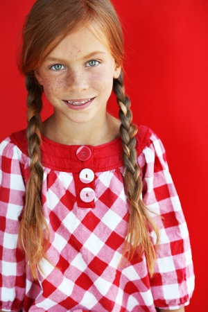 7 8 years: Cute redheaded child on red background Stock Photo