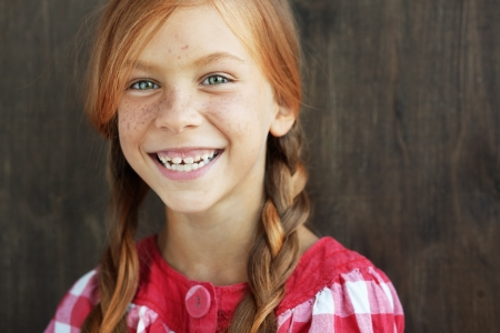 7 years old: Cute redheaded child on vintage brown background