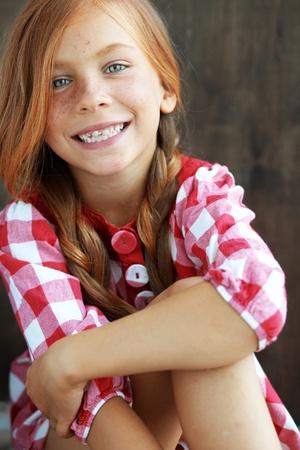 Nette rothaarige Kind auf Vintage-braunem Hintergrund