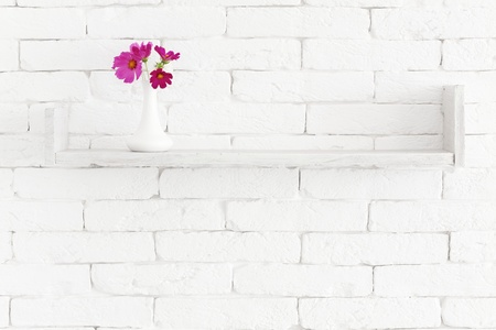 Decorative shelf on white brick wall with flowers in vase on it Stock Photo - 21591654