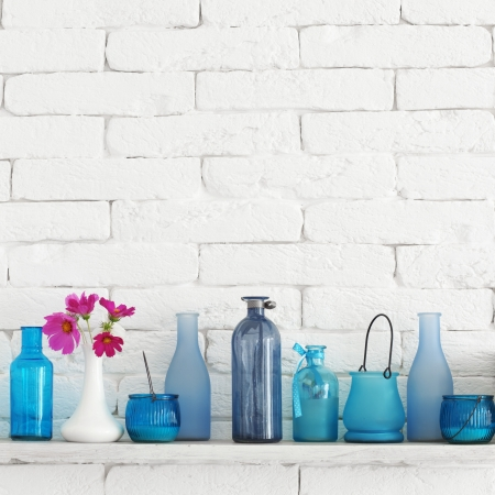 glass vase: Decorative shelf on white brick wall with blue bottles on it