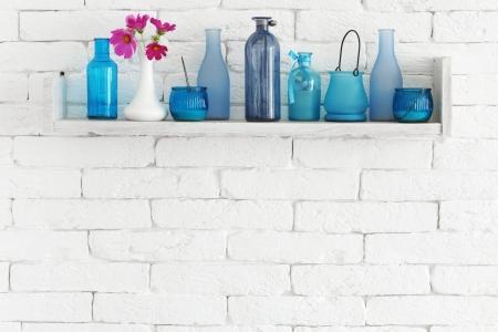 Decoratieve plank op witte bakstenen muur met blauwe flessen op het