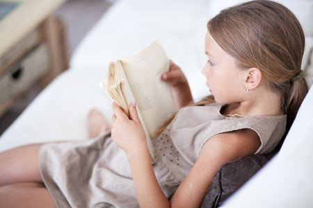 girl reading book: Portrait of 7 years old child reading book on the sofa at home