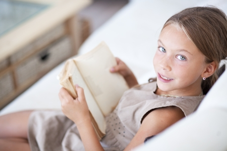 8 years: Portrait of 7 years old child reading book on the sofa at home
