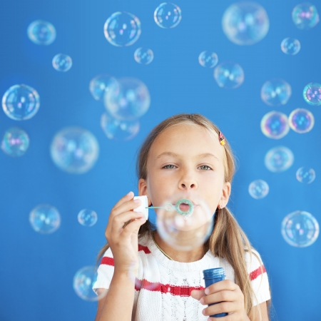 7 8 years: Portrait of funny lovely little girl blowing soap bubbles Stock Photo